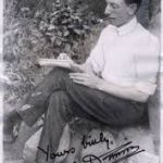 CJ Dennis sitting on rocks in the garden of Sunnyside where he wrote some of The Sentimental Bloke. He is dressed in dark pants and a light coloured shirt, fully buttoned but without a tie. He is sitting with his legs crossed and a writing pad balanced on his knee. He appears to be writing and his pipe is in his mouth.