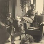 CJ Dennis and his wife Biddy posing in armchairs in room at their home Arden. CJ is sitting in an armchair with his legs crossed and an arm casually resting on the arm of the chair. Biddy is sitting on the arm of a second chair closer to a window with CJ's banjo displayed on the chair itself. Their dog lays at their feet. There is a lamp with a shawl draped over it in the background.